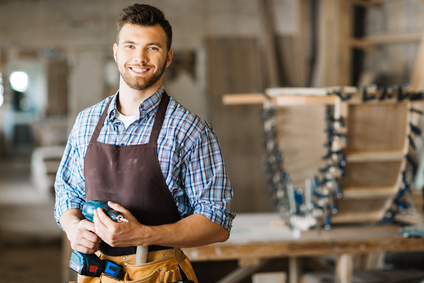 Smiling craftsman with electric drill